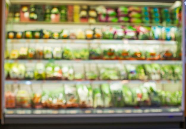 Defokussiert verwischt ein einkaufsregal gemüse und obst, das sie bei lebensmitteln im supermarkt anziehen.