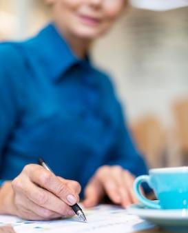 Defokussierte ältere geschäftsfrau, die kaffee trinkt und an papieren arbeitet
