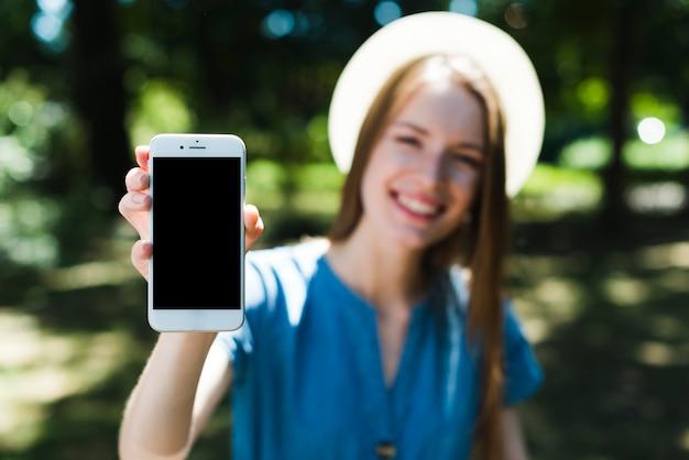 Defokussierte frau, die modell smartphone hält