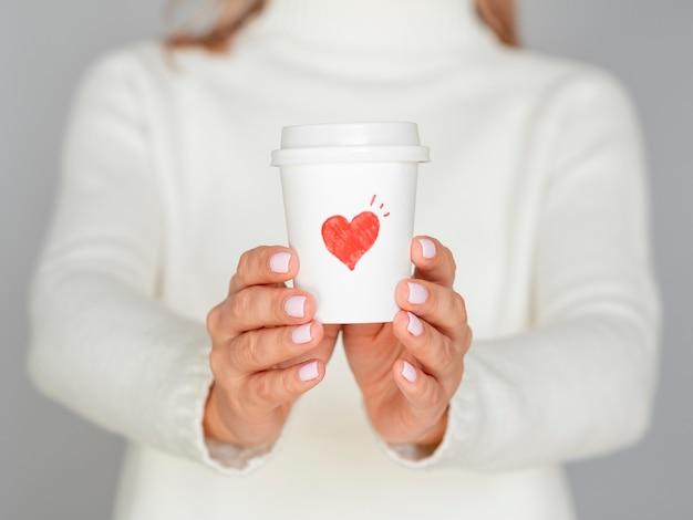 Defokussierte frau, die valentinsgrußkaffee hält