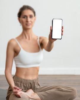 Defokussierte frau zu hause, die yoga macht und smartphone hält