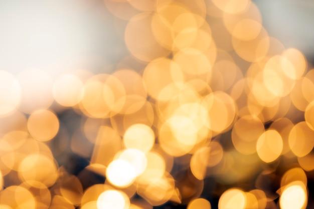 Defokussierte goldene helle abstrakte weihnachts- oder feiertagshintergrundtextur, funkelnde gelbe verschwommene warme töne