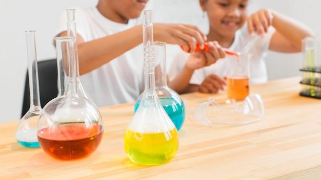 Defokussierte mädchen, die mit tränken und chemie experimentieren