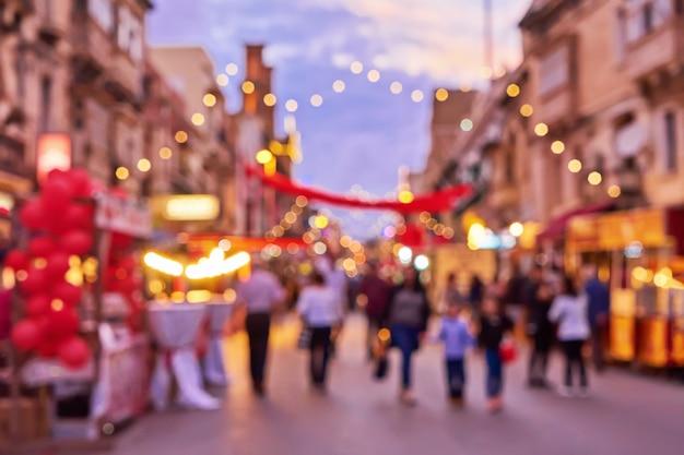Defokussierte menschenmenge während des weihnachtsmarkts eine alte stadtstraße
