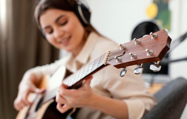Defokussierte musikerin, die zu hause akustikgitarre spielt