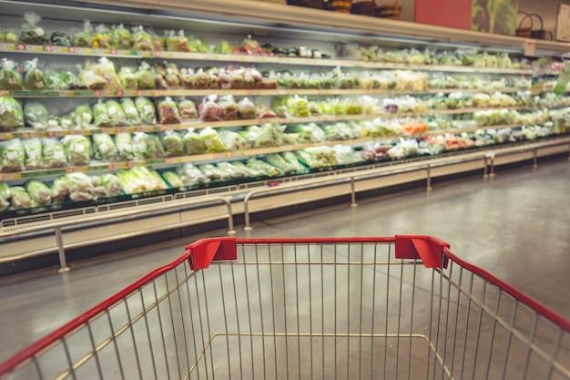 Defokussierte unschärfe, die einen einkaufswagen kauft, der im supermarkt auf dem boden gemüselebensmittel kauft?