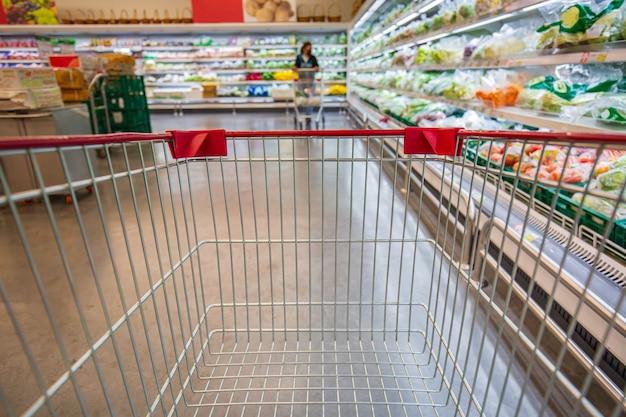 Defokussierte unschärfe, die einen weiblichen einkaufswagen kauft, der im supermarkt auf dem boden gemüselebensmittel kauft?