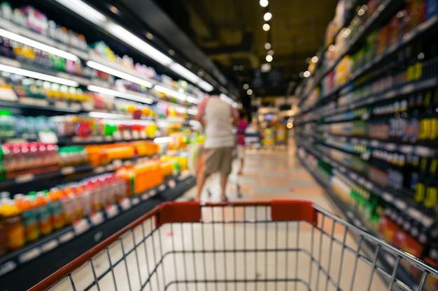 Defokussierte unschärfe von männlichen und weiblichen einkaufswagen, die beim einkaufen von alkoholischen getränkeprodukten im supermarkt einkaufen?