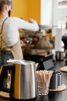 Defokussierte weibliche barista mit kaffeemaschine