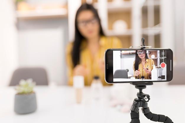 Defokussierte weibliche vloggerin zu hause mit smartphone