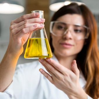 Defokussierte wissenschaftlerin mit reagenzglas