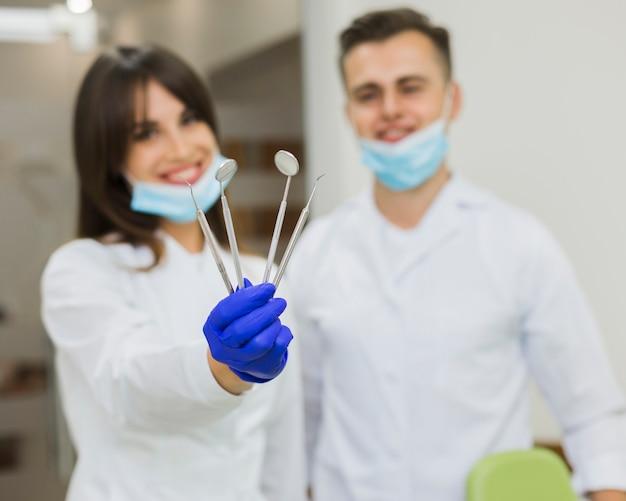 Defokussierte zahnärzte, die zahnmedizinische ausrüstung halten