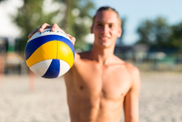 Defokussierter hemdloser männlicher volleyballspieler am strand, der ball hält