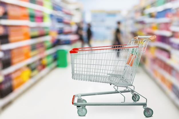 Defokussierter hintergrund der supermarktgangunschärfe mit leerem roten einkaufswagen
