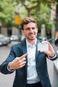 Defokussierter junger geschäftsmann, der seinen finger in richtung zur visitenkarte zeigt