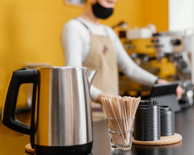 Defokussierter männlicher barista an der theke mit wasserkocher