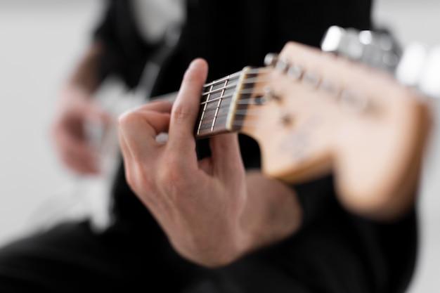 Defokussierter männlicher musiker, der e-gitarre spielt