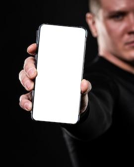 Defokussierter männlicher rugbyspieler, der smartphone hält