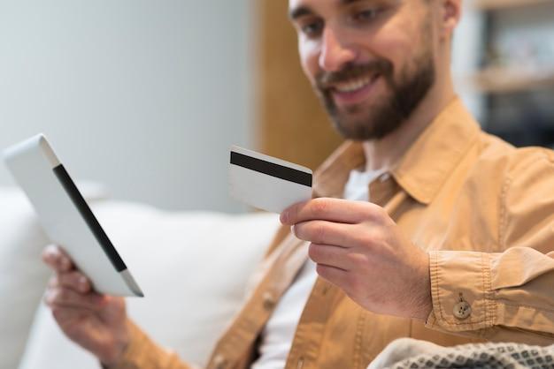 Defokussierter mann, der kreditkarte und tablette hält