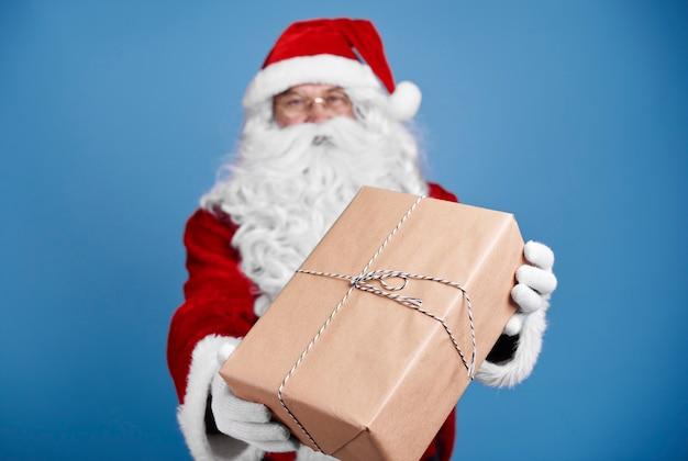 Defokussierter weihnachtsmann, der weihnachtsgeschenke gibt