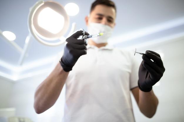 Defokussierter zahnarzt mit zahnheilkundeinstrumenten