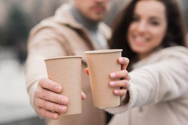 Defokussiertes paar, das kaffeetassen hält
