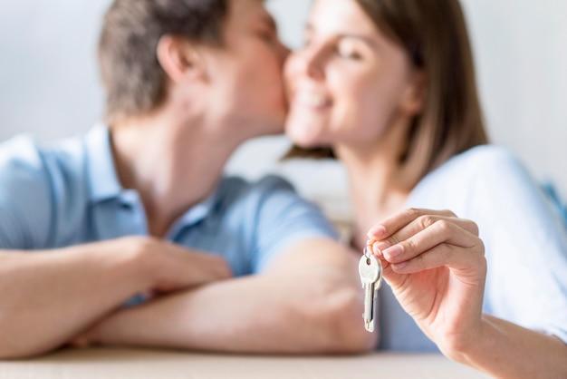 Defokussiertes paar, das küsst, während schlüssel für neues zuhause gehalten werden