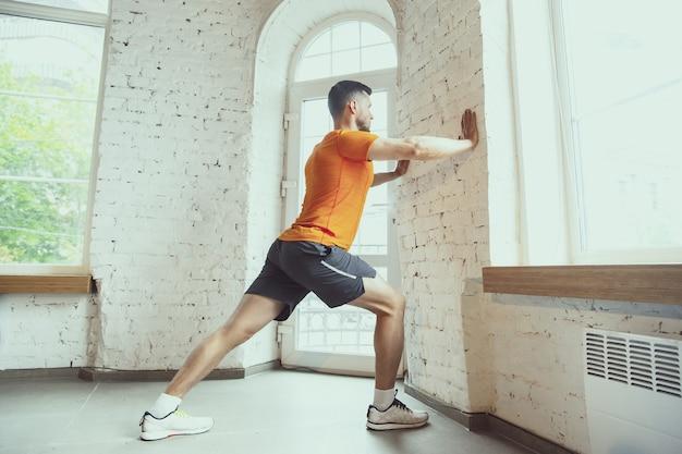 Dehnen. junger kaukasischer mann trainiert zu hause während der quarantäne des coronavirus-ausbruchs, macht fitnessübungen, aerobic. sportlich bleiben während der isolierung. wellness, sport, bewegungskonzept.