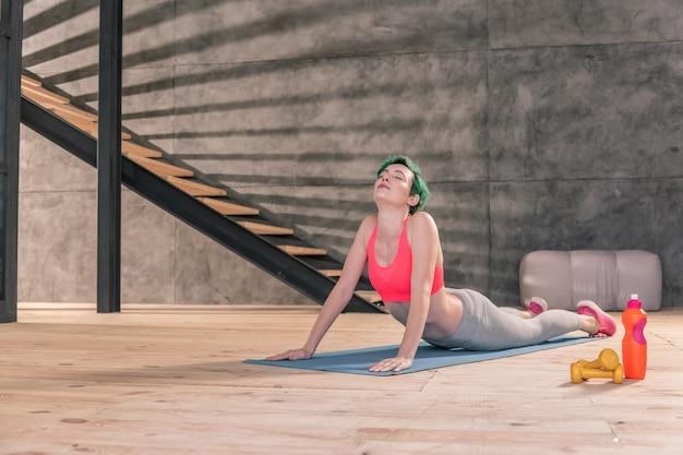 Dehnen nach dem fitnessstudio. junge schlanke und gesunde frau mit hellgrünem haar, das sich nach dem fitnessstudio ausdehnt