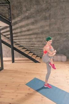 Dehnen nach dem lauf. ansprechende junge sportlerin mit rosa turnschuhen, die sich nach dem laufen die beine ausstrecken