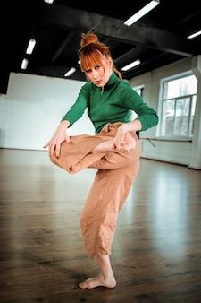 Dehnen. rothaarige professionelle choreografin mit haarbüschel, die ihre beine streckt, während sie im studio tanzt