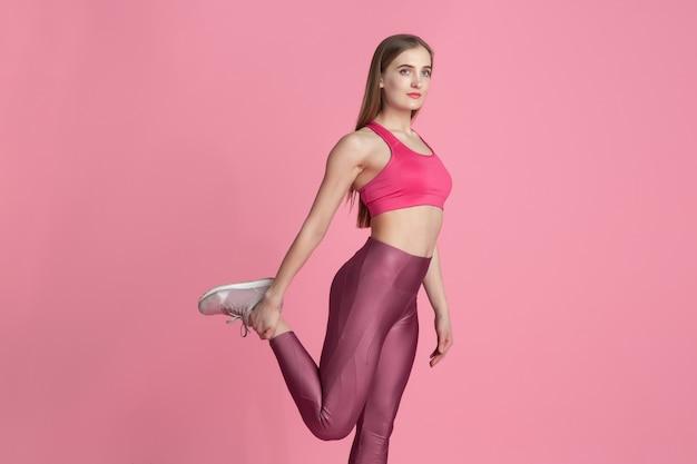 Dehnen. schöne junge sportlerin, die im studio übt, einfarbiges rosa porträt. kaukasisches modelltraining mit sportlicher passform. bodybuilding, gesunder lebensstil, schönheits- und aktionskonzept.