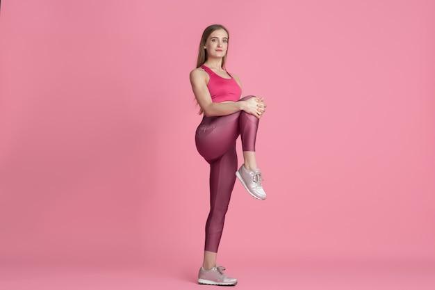 Dehnen. schöne junge sportlerin, die im studio übt, einfarbiges rosa porträt.