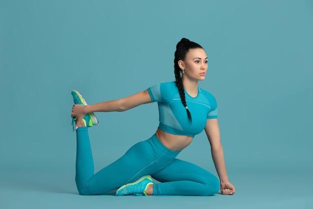 Dehnen. schöne junge sportlerin üben, einfarbiges blaues porträt. sportlich fit brünettes model training. wellness, gesunder lebensstil, schönheit, bewegung und aktionskonzept.