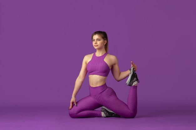 Dehnen. schöne junge sportlerin üben, einfarbiges lila porträt. sportliches kaukasisches fit-model-training. bodybuilding, gesunder lebensstil, schönheits- und aktionskonzept.