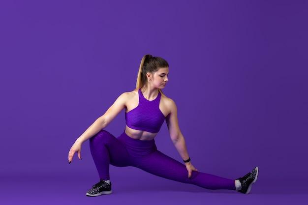Dehnen. schöne junge sportlerin üben, einfarbiges lila porträt. sportliches kaukasisches fit-modelltraining. bodybuilding, gesunder lebensstil, schönheits- und aktionskonzept.
