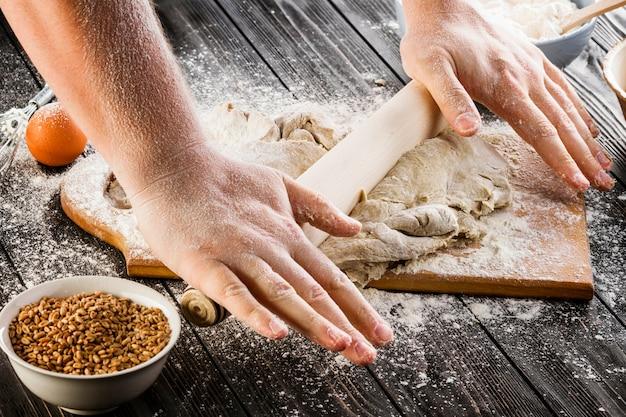 Dehnend teig des bäckers mit einem nudelholz und einem mehl über dem hackenden brett auf holztisch