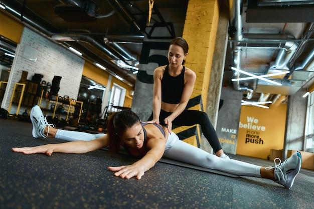 Dehnübungen. junge flexible fitnessfrau in sportbekleidung, die mit hilfe ihres personal trainers im fitnessstudio querfäden übt. sport und gesundes lifestyle-konzept