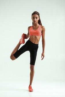 Dehnübungen. voller länge der jungen afrikanischen frau mit perfektem körper, der ihr bein ausdehnt, während sie vor grauem hintergrund steht. sportkonzept. aktiver lebensstil