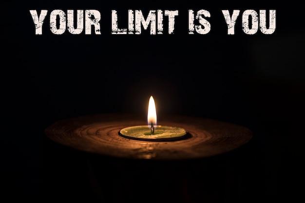 Dein limit bist du - weiße kerze mit dunklem hintergrund - in einem holzkerzenständer.