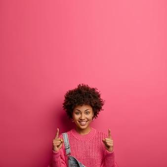 Dein logo hier. erfreute lächelnde frau mit afro-haarspitzen und fördert etwas nach oben, sagt folge dieser richtung, trägt strickpullover, isoliert auf rosa wand. vermarktung und werbung