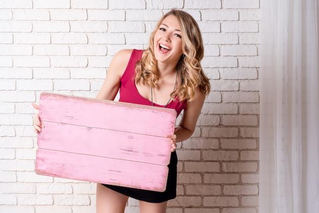Dein text hier. recht junge lächelnde blondine, die leeres leeres brett halten. studioporträt mit weißer backsteinmauer auf hintergrund.