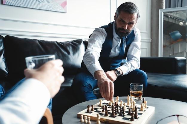 Deine bewegung! zwei junge hübsche männer in vollen anzügen, die schach spielen und lächeln, während sie drinnen sitzen.