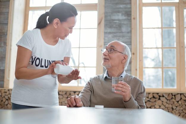 Deine medikamente. junger angenehmer freiwilliger, der bleibt, während pillen dem älteren mann vorschlägt, der glas hält, geht wasser