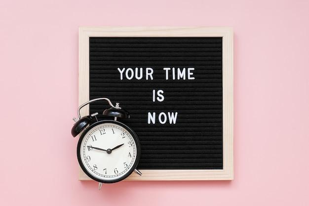 Deine zeit ist jetzt. motivzitat auf briefkasten und schwarzem wecker auf rosa hintergrund