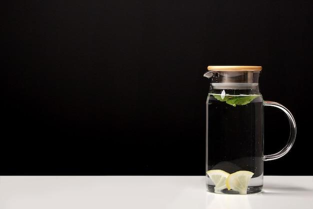 Dekanter mit sauberem kaltem wasser mit zitrone und minze