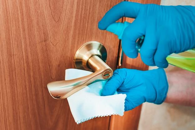 Dekontamination des metalltürgriffs. entfernen von keimen aus dem griff an der vordertür. mit einem desinfektionsmittel und einem lappen in die hand einer frau einsprühen. die putzfrau reinigt die wohnung. blaue handschuhe