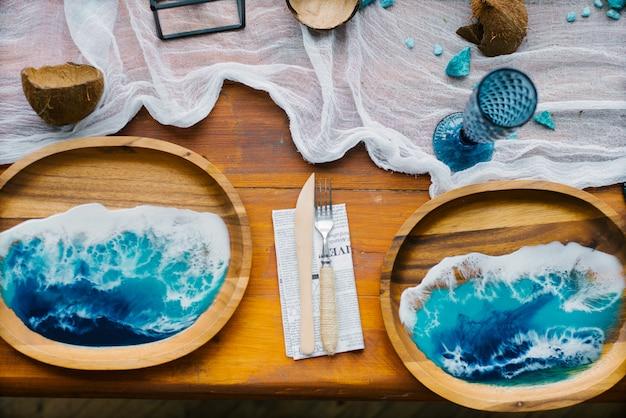 Dekor im tropischen oder maritimen stil in der dekoration des festlichen gedecks. farbe des jahres 2020, klassisches blau. holzplatte mit epoxidharz in form von ozean oder meereswelle