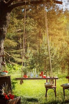 Dekor romantisches abendessen mit kerzen, blumen im grünen wald bei herrlichem sonnenuntergang.