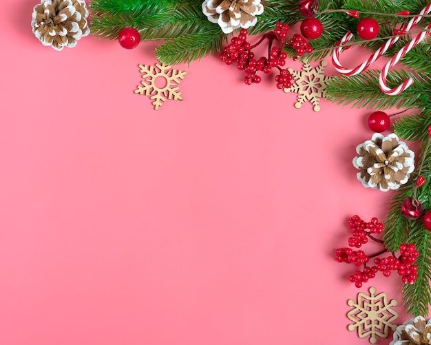 Dekor - weihnachtsbaumast, eberesche, kegel, lutscher, schneeflocke auf rosa hintergrund flach zu legen